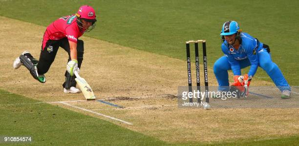 Alyssa Healy of the Sixers makes her ground as Tegan McPharlin of the Strikers gathers the ball during the Women's Big Bash League match between the...