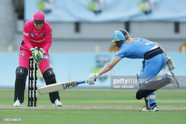 Alyssa Healy of the Sixers runs out Katie Mack of the Strikers during the Women's Big Bash League WBBL match between the Sydney Sixers and the...