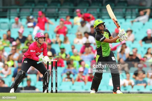 Alyssa Healy of the Sixers watches on as Harmanpreet Kaur of the Thunder bats during the Women's Big Bash League match between the Sydney Sixers and...