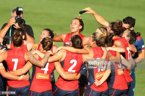 Alyssa Misfud of the Demons sings the club song after winning with teammates during the round two AFLW match between the Melbourne Demons and the...