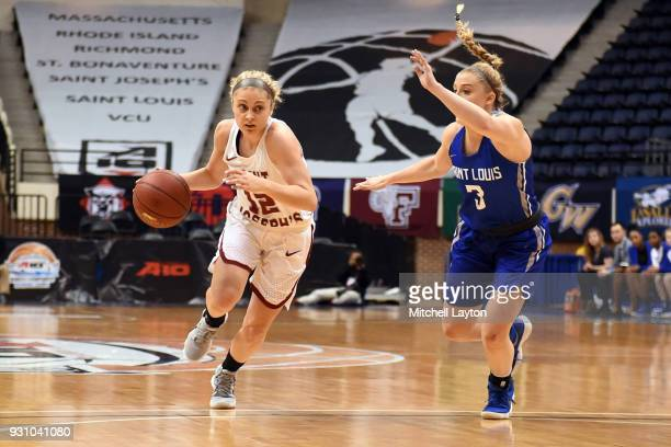 Alyssa Monaghan of the St Joseph's Hawks dribbles by Jackie Kemph of the Saint Louis Billikens during the semifinal round of the Atlantic10 Women's...