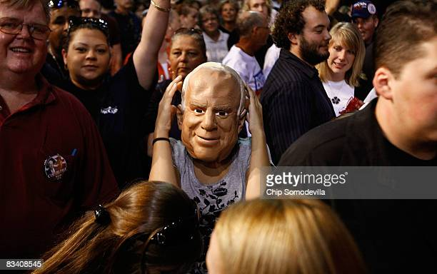 Alyssa Salerno of Sarasota Florida wears a mask resembling Republican presidential nominee John McCain before a campaign rally at the Robarts Arena...