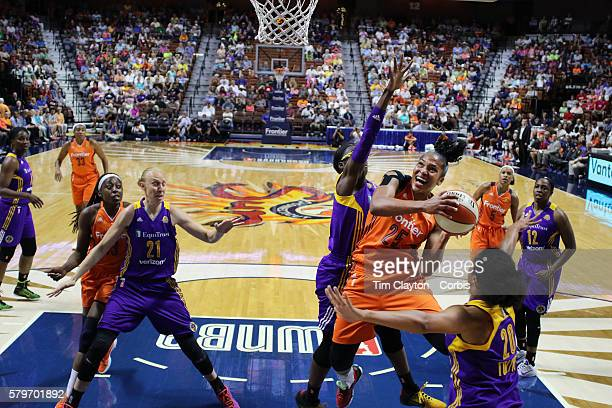 Alyssa Thomas of the Connecticut Sun drives to the basket defended by Essence Carson of the Los Angeles Sparks and Kristi Toliver of the Los Angeles...