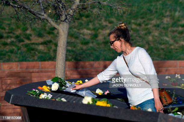 Alyssa Welling of Denver Colorado places flowers at the Columbine Memorial at Clement Park in Littleton Colorado before a community vigil for the...