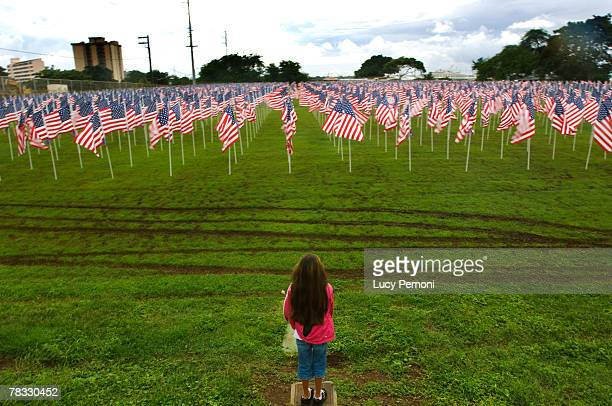 Alyssah Ruff of Pearl Harbor Hawaii stands near the edge of the Healing Field a memorial of 2500 flags overlooking the Arizona Memorial during the...