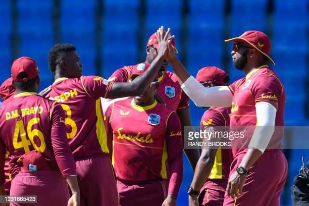 Alzarri Joseph and Kieron Pollard of West Indies celebrate the dismissal of Dimuth Karunaratne of Sri Lanka during the 2nd ODI match between West...