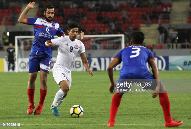 AlZawraa's Hussein Ali dribbles the ball as Manama's Masoud Qambar defends during the AFC Cup football match between Iraq's AlZawraa club and...