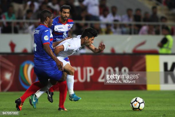 AlZawraa's Hussein alSaedi dribbles the ball between Manama's Luis Gustavo Camilo and Ali Haram during the AFC Cup football match between Iraq's...