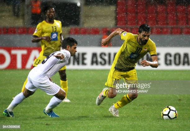 AlZawraa's Hussein AlSaedi vies for the ball against AlAhed's Mohamad Haidar during the AFC Cup football match between Iraq's AlZawraa club and...