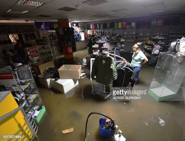 Am employee of a shop in the center of Kiev save the retail items from floods following a heavy overnight storm on August 16 2018 Some 200 trees and...