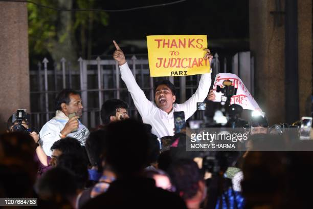 Am indian man holds a placard and shout slogans outside the gates of Tihar Jail after the execution of four men convicted in the gangtape and murder...
