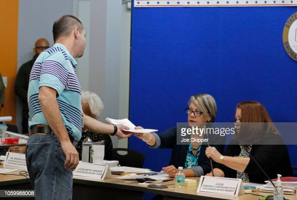 Am member of the Canvassing Board of Broward County Supervisor of Elections hands signed results to an official after they were transmitted to the...