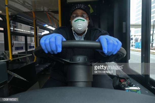 A bus driver for the Detroit Michigan city bus line DDOT poses for a portrait wearing a protective mask and gloves for protection in Detroit Michigan...