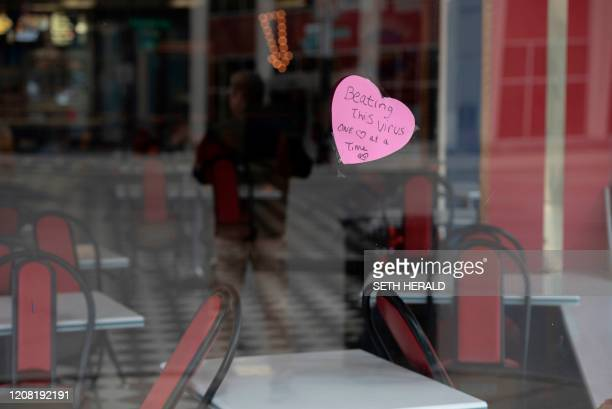 TOPSHOT A sign hangs in the window of American Coney Island restaurant in Detroit Michigan reading Beating this virus one heart at a time on March 24...