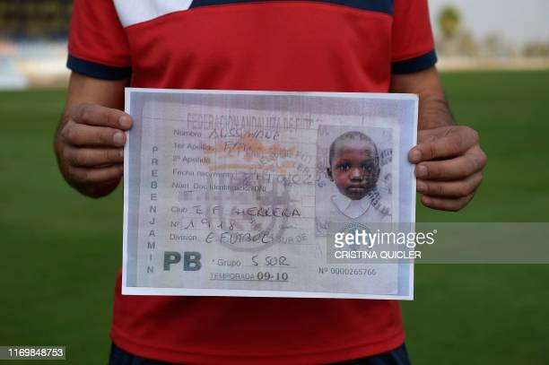 Amador Saavedra under 10s team's coach at the Peloteros football school holds a picture depicting the 2009/2010 season federative card of...
