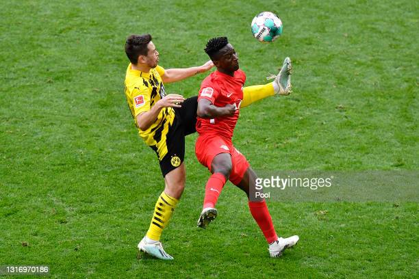 Amadou Haidara of RB Leipzig is challenged by Raphael Guerreiro of Borussia Dortmund during the Bundesliga match between Borussia Dortmund and RB...