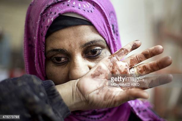 Amal AbuRqayiq wipes the sweat from her face in her small carpentry workshop in the Nusseirat refugee camp in the Gaza Strip on February 27 2014 Amal...