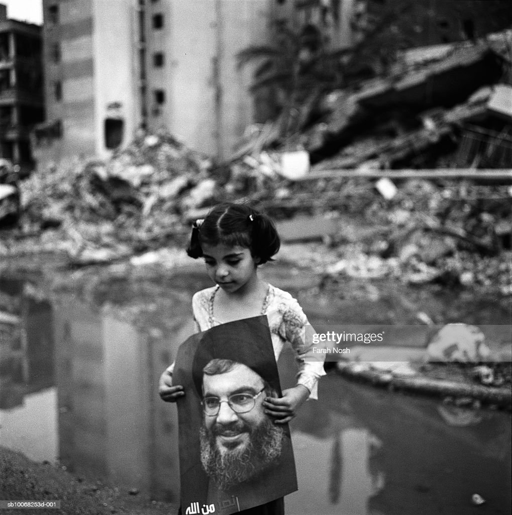 Amal, 7, carries a poster of Hezbollah leader Hassan Nasrallah among the rubble on August 31, 2006 in Dahiya, the southern suburb district of Beirut. The 2006 conflict between Hezbollah and Israeli military forces started on July 12, 2006 and continued until a United-Nations ceasefire on August 14, 2006. The conflict killed over 1,500 people, most of whom were Lebanese civilians, severely damaged Lebanese infrastructure, and displaced hundreds of thousands. Even after the ceasefire, much of South Lebanon remained uninhabitable due to unexploded cluster bombs.