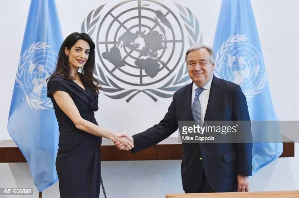 Amal Clooney and 9th SecretaryGeneral of the United Nations António Guterres shake hands at United Nations Headquarters on March 10 2017 in New York...
