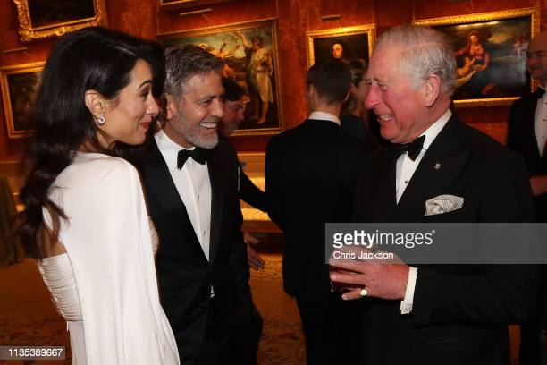 Amal Clooney and George Clooney speak to Prince Charles Prince of Wales as they attend a dinner to celebrate The Prince's Trust hosted by Prince...