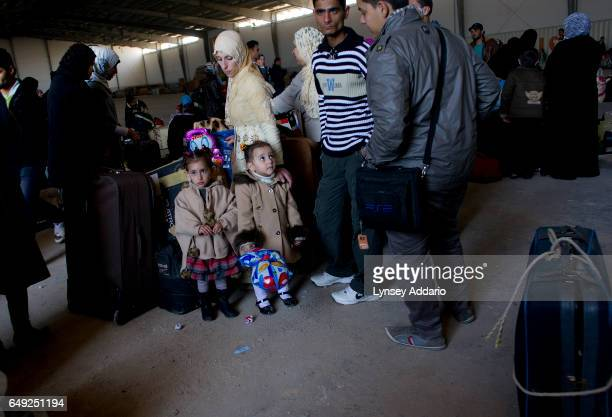 Amal Dora stands with her twin daughters Noor left and Hadir right as they wait with other Syrian families to board a ship to take them out of...