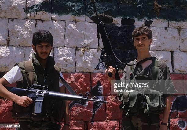 Amal militia men armed with M16 automatic assault rifles stand in front of Lebanon flag painted on a wall during the civil war 10th June 1986