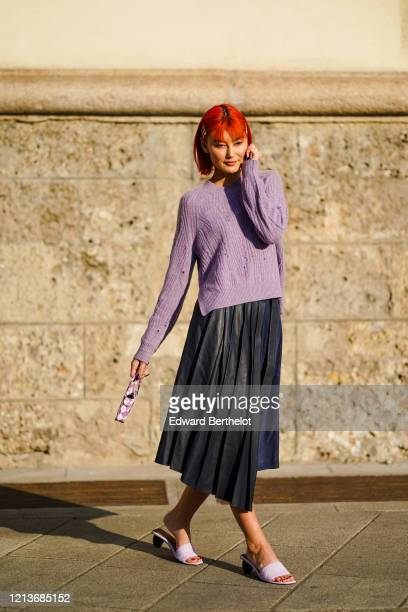 Amalie Gassman wears hair clips, a mauve sweater, a black leather pleated skirt, a small white and mauve handbag with diamond patterns, mauve mules...