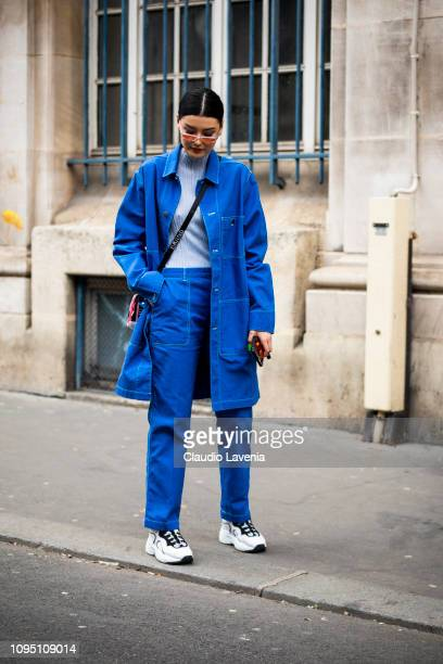 Amalie Gassmann wearing a blue long jacket blue matching trousers white shoes orange sunglasses and cross body bag is seen in the streets of Paris...