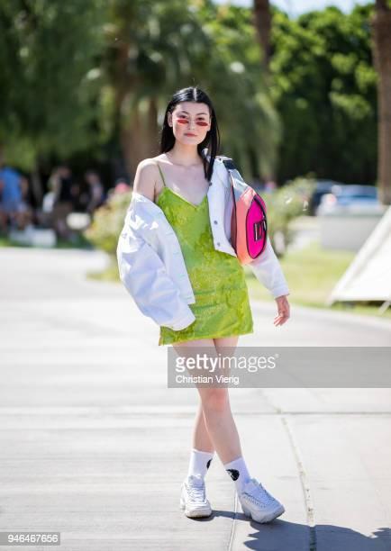 Amalie Gassmann wearing short green dress white jacket fanny bag sneaker is seen at Revolve Festival on April 14 2018 in Indio California