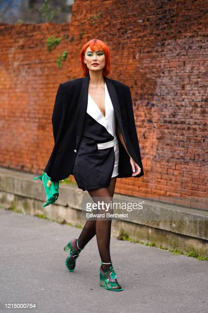 Amalie Gassmann wears a black oversized blazer jacket, a black and white lustrous silky dress, a green Balmain bag with fringes, black tights, green...
