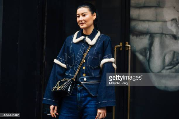 Amalie Gassmann wears a denim jacket with lining jeans and a black Dior bag outside the Alexis Mabille show at Salle Pleyel on January 23 2018 in...