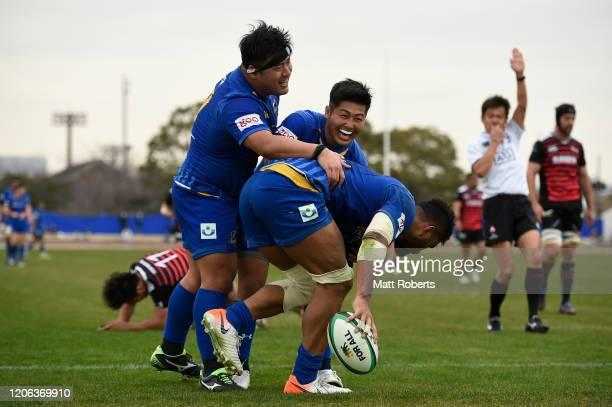 Amanaki Lelei Mafi of NTT Communications ShiningArcs celebrates scoring a try with Ken Saito and Shotaro Matsuo during the Rugby Top League match...