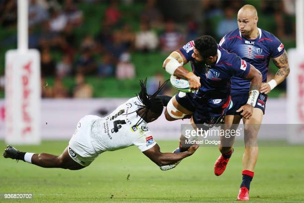 Amanaki Mafi of the Rebels tries to pass the ball to Bill Meakes while being tackled by S'busiso Nkosi of the Sharks during the round six Super Rugby...