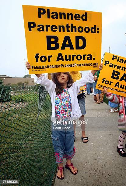 Amanda Borrego carries a sign during a protest at the opening of a Planned Parenthood clinic October 2 2007 in Aurora Illinois The clinic reported to...