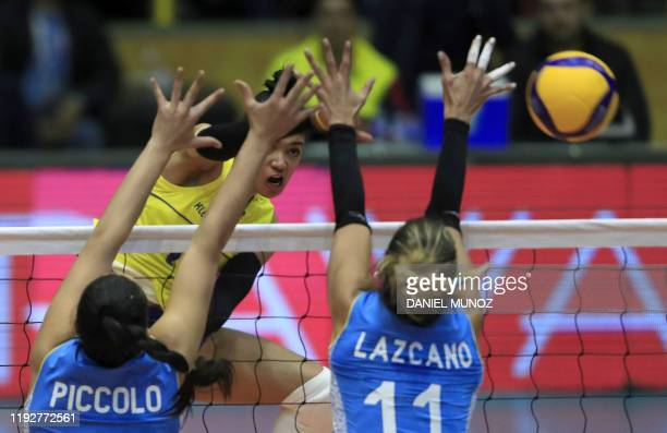 Amanda Coneo of Colombia spikes the ball against Sol Piccolo of and Julieta Lazcano of Argentina during their women's Tokyo 2020 Volleyball...