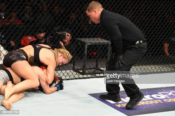 Amanda Cooper attempts to submit Angela Magana as referee Keith Peterson monitors in their women's strawweight bout during the UFC 218 event inside...