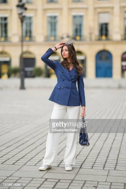 Amanda Derhy @amanda_jashley wears black sunglasses, pearls earrings, a gold pendant necklace, a black t-shirt, a navy blue long blazer jacket,...