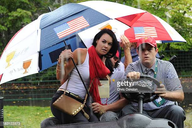 Amanda Dufner sits on Jason Dufner of the US Team as they shelter from the rain during the Day Two FourBall Matches of The Presidents Cup at the...