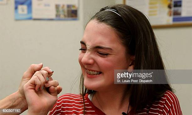 Amanda Eshelman grabs her mother's hand as she started to cry on Thursday Dec 1 at St Louis Children's Hospital in St Louis Mo Her audiologist Amy...