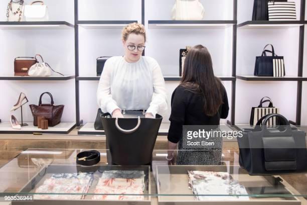 Amanda Fulton left shows Erin Taff a bag at Max Mara's Newbury St location as it celebrates Boston ICA's Watershed Gala on May 1 2018 in Boston...