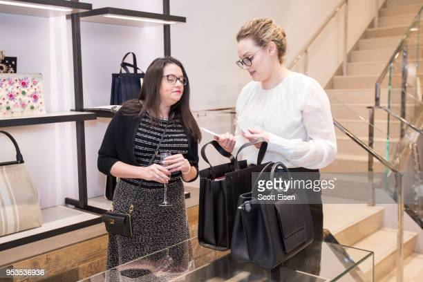 Amanda Fulton right shows Erin Taff a bag at Max Mara's Newbury St location as it celebrates Boston ICA's Watershed Gala on May 1 2018 in Boston...