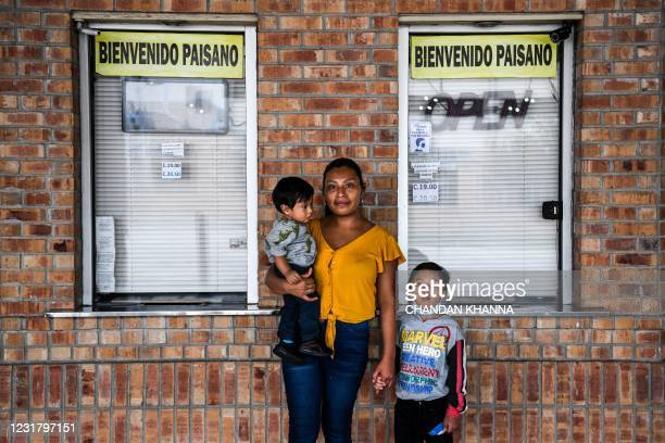 Amanda Garcia , a migrant form Guatemala, poses with her sons Lauro Garcia and Wilson Garcia as they wait for a bus at a station near the Gateway...