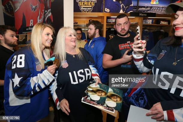 Amanda Kessel of the gold medal winning USA Olympic Women's Hockey Team poses for a picture with a fan during a visit to the NHL Headquarters and the...