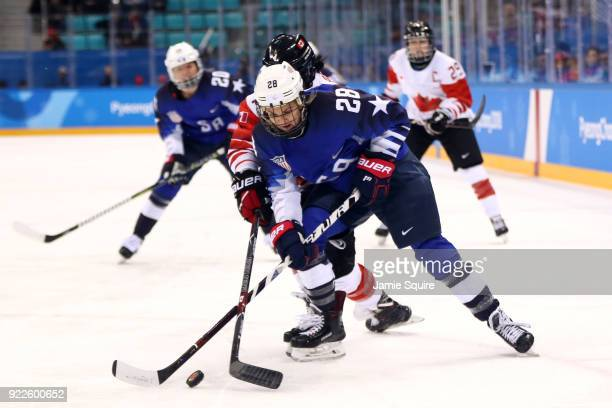Amanda Kessel of the United States battles for the puck with Brigette Lacquette of Canada in the first period during the Women's Gold Medal Game on...