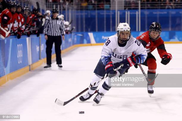 Amanda Kessel of the United States controls the puck against Rebecca Johnston of Canada during the Women's Ice Hockey Preliminary Round Group A game...