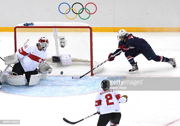 Amanda Kessel of United States stretches for the puck on the goal line next to Florence Schelling of Switzerland during the Women's Ice Hockey...
