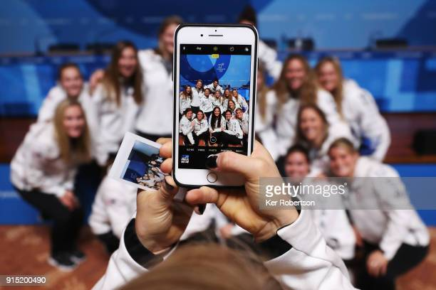 Amanda Kessel takes a picture of her United States Women's Ice Hockey team mates while they attend a press conference at the Main Press Centre during...