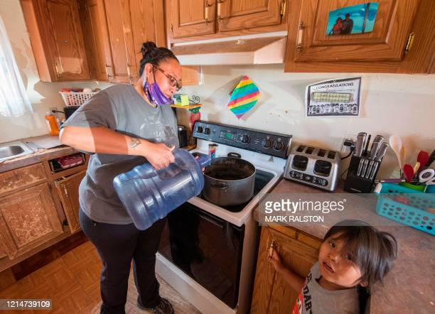 Amanda Larson who has no running water at home, carries water for her son Gary Jr to have a bath in the Covid-19 virus affected Navajo Nation town of...