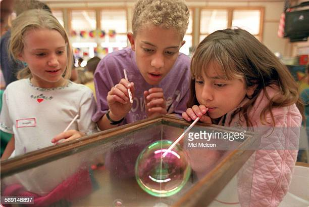 Amanda Lee left 2nd grader and Neil Ross 4th grader watch Ashley Quezada 2nd grader at Conejo elementary school in Thousand Oaks as she blows a...