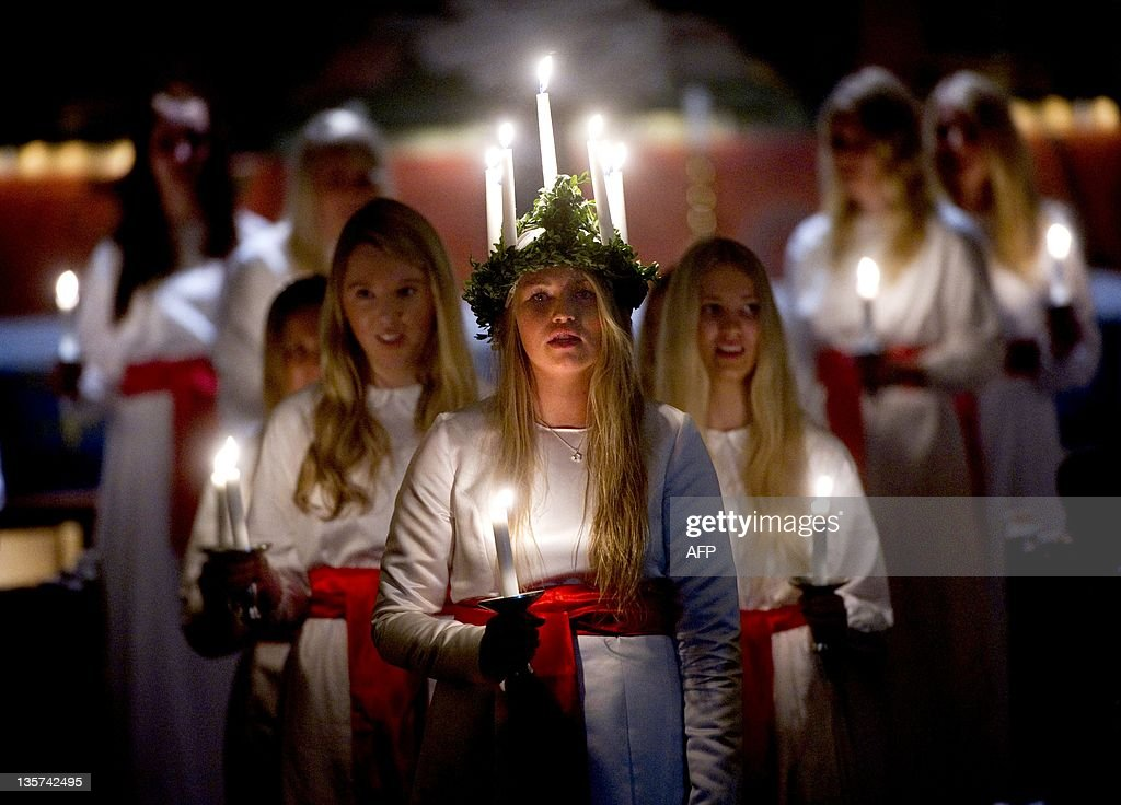 Amanda Lindblom (C) performs as Santa Lucia with her twelve Lucia handmaidens during the traditional Queen of Light procession arranged by the Swedish church at Varfru church in Enkoping, 73 kms northwest of capital city Stockholm, on December 13, 2011.